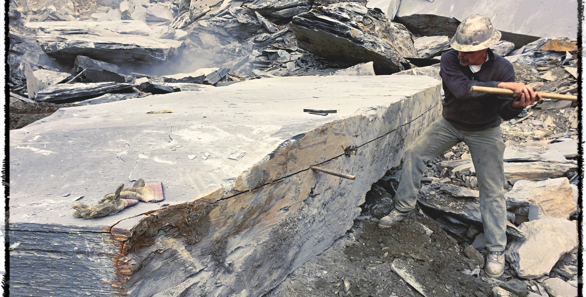 Working up a block of slate in quarry.