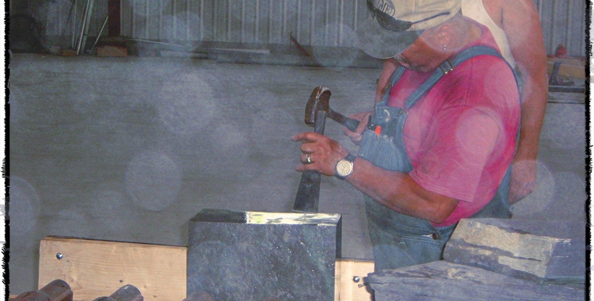 Slate worker splitting roofing slate.